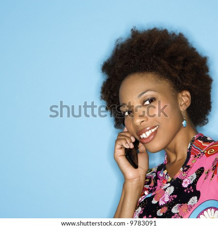 Woman with afro wearing vintage print fabric smiling holding cellphone. - stock photo