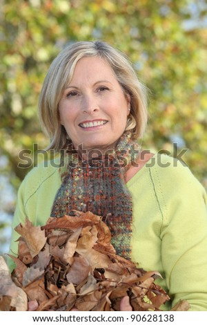 Woman with an armful of autumnal leaves - stock photo