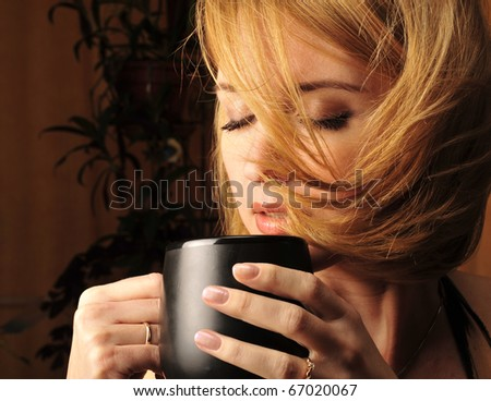 Woman with an aromatic coffee in hands sitting in armchair in dark room with romantic light - stock photo