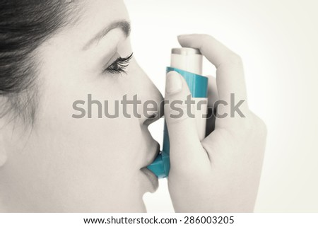 Woman with an asthma inhaler against white background - stock photo