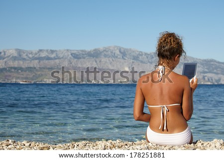 Woman with an e-reader on vacation at the beach reading a book.  - stock photo