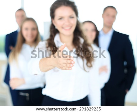 woman with an open hand ready for handshake in office - stock photo
