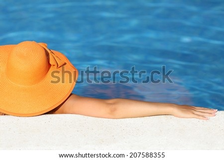 Woman with an orange picture hat bathing relaxed in a pool water enjoying vacations with blue background      - stock photo