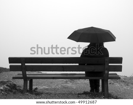 Woman with an umbrella sitting on a bench at a cliff edge - stock photo