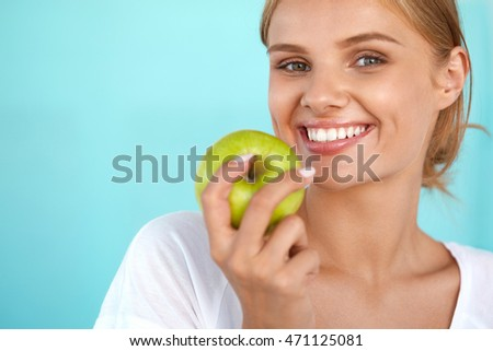 Woman With Apple. Closeup Portrait Of Beautiful Happy Smiling Girl With White Smile, Healthy Teeth Holding Natural Organic Green Apple. Dental Health, Healthy Eating Concepts. High Resolution Image
