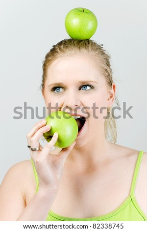 Woman with apple on her head eating an apple