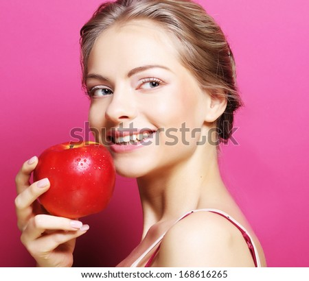 woman with apple over pink background - stock photo