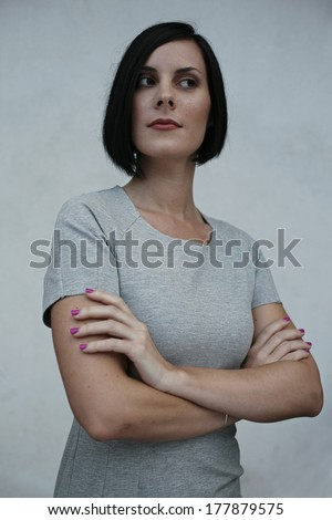 woman with arms crossed on her chest looking away, isolated on blue background, portrait of a young woman stands with his arms crossed over her chest