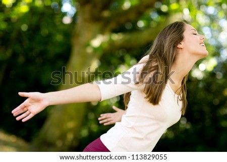 Woman with arms open enjoying her freedom at the park - stock photo
