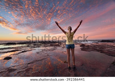 Woman with arms outstretched towards the sunrise sky celebrating life.  Jubilation, triumph, success, spiritual, exhilaration,