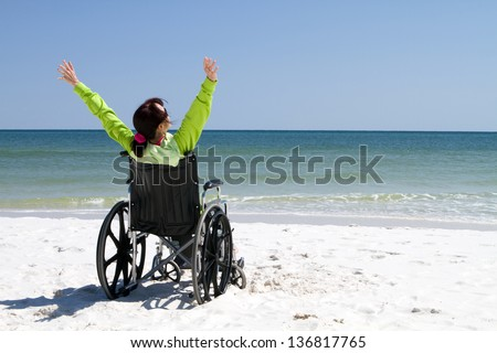Woman with arms raised celebrates her achievement and success in the sunshine even with her disabilities in a wheelchair. - stock photo