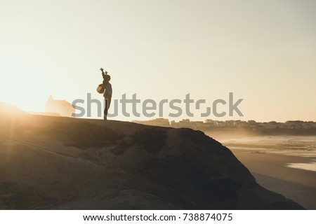 Woman with arms raised enjoying the view at sunset