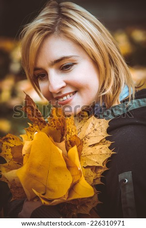 woman with autumn leaves in hand and fall yellow maple garden background - stock photo