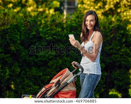 Woman With Baby Carriage Using Cell Phone