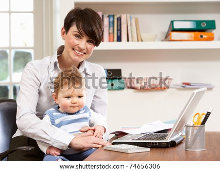 Woman With Baby Working From Home Using Laptop - stock photo