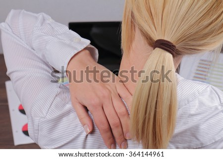 Woman with back pain. Business woman rubbing his painful neck close up - stock photo