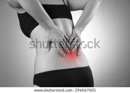 Woman with backache. Pain in the  human body. Black and white photo with red dot - stock photo