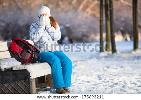 Woman with backpack heating hands in mittens at winter, copyspace - stock photo