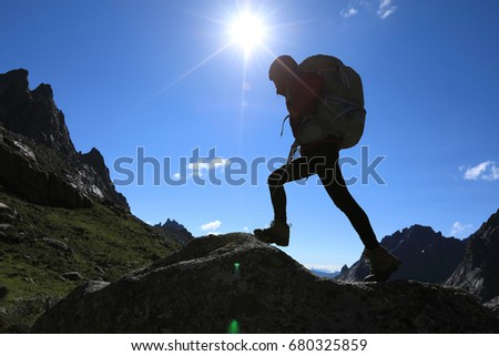 woman with backpack hiking in mountains travel lifestyle success concept