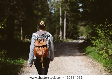 Woman with backpack on a path throught the forest - stock photo