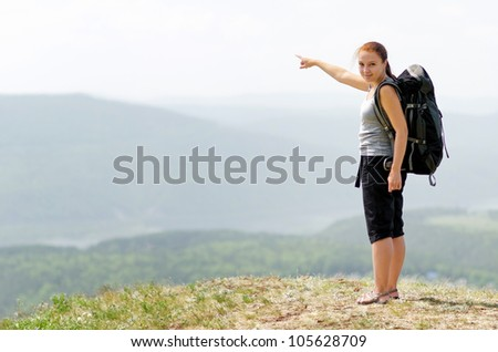 Woman with backpack on green hill.