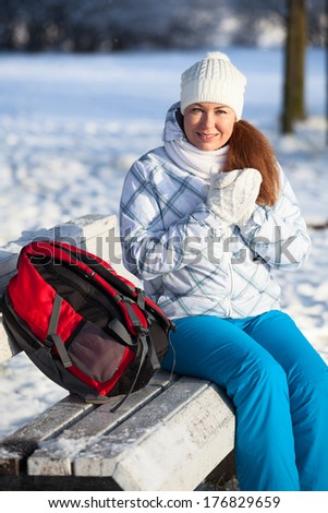 Woman with backpack resting on a bench in winter park - stock photo