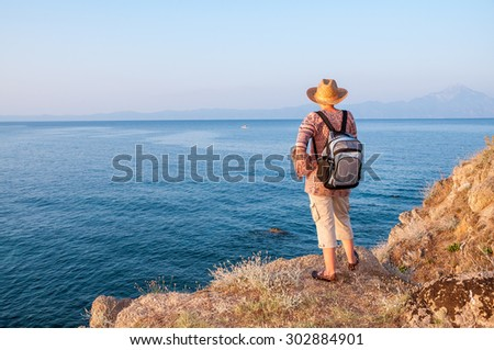 Woman with backpack standing on the top of the mountain and enjoying the sea view and the mountain in the distance - stock photo