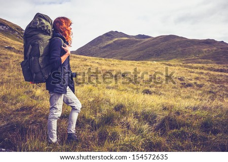 Woman with backpack trekking through the wilderness - stock photo