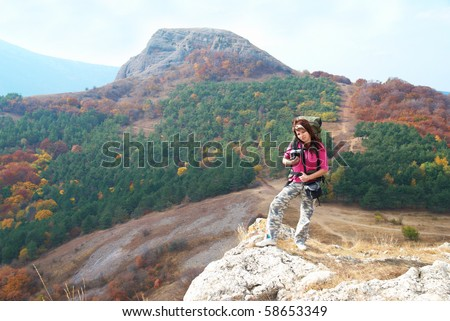 Woman with backpack viewing at the landscape - stock photo
