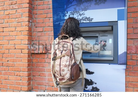 Woman with backpack withdrawing money from credit card at ATM.  - stock photo