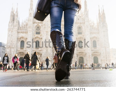 woman with bag in front of of Duomo di Milano (Milan Cathedral), Milan, Italy - stock photo