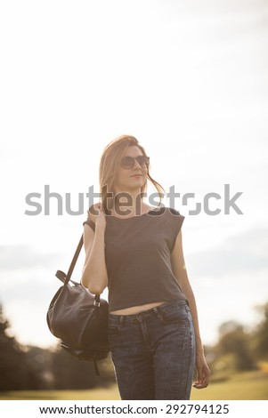 Woman with bag in the sunlight, soft focus, overexposed - stock photo
