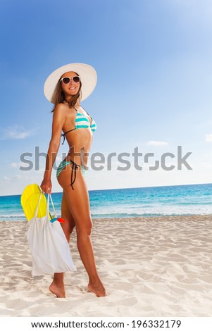 Woman with bag walking to the beach - stock photo