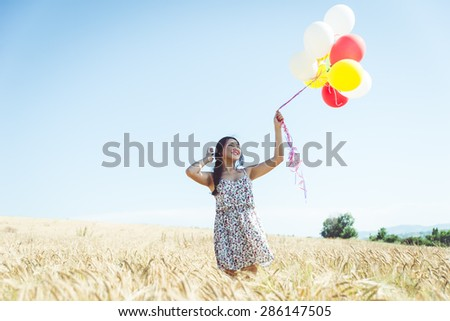 woman with balloons in a wheat field. concept about carefree, airiness and people - stock photo