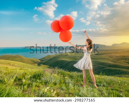 Woman with balloons in field grass on mountains a beautiful landscape outdoors. Girl playing with balloons in the holiday.