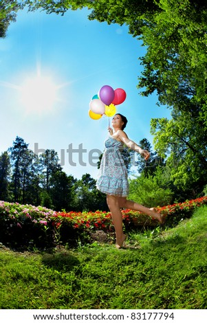 Woman with balloons in the park on grass - stock photo