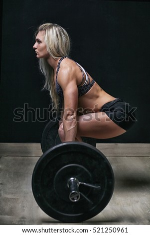 woman with barbell on a black background
