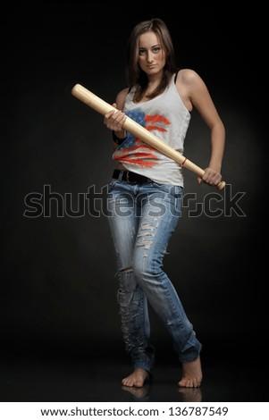 Woman with baseball bat on black background - stock photo
