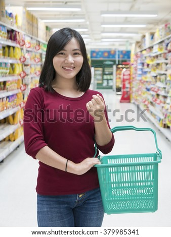 Woman with basket walking in supermarket