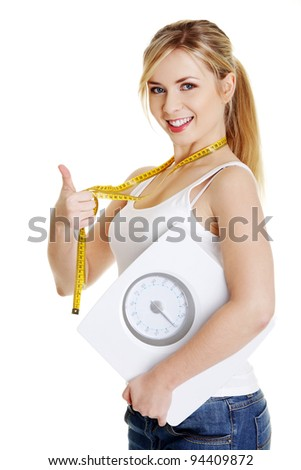 Woman with bathroom scale and measuring tape gesturing OK, isolated on white - stock photo
