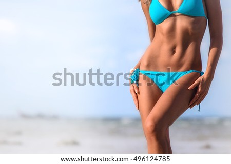 Woman with beautiful body in bikini posing on beach