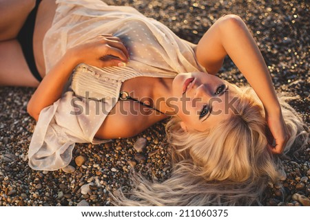 Woman with beautiful body on a tropical beach. Beautiful young woman relaxing on the beach. beautiful woman in a bathing suit standing on the beach at sunset. Portrait of the beautiful girl close-up - stock photo