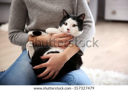 Woman with beautiful cat on carpet, indoor - stock photo