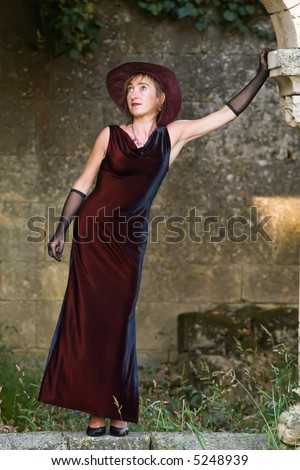 woman with beautiful dress posing in ancient abbey ruins at sunset