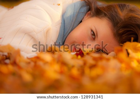 Woman with beautiful eyes laying in autumn leaves - stock photo