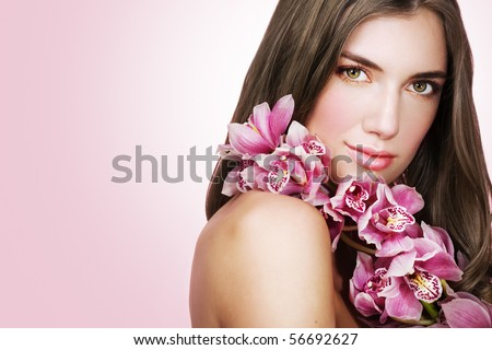 Woman with beautiful makeup and pink orchids. Space for text. - stock photo