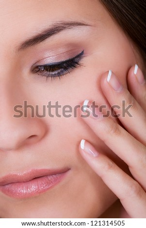 Woman with beautiful manicured finger nails covered in cleared gloss lacquer or nail varnish holding her hand to her cheek