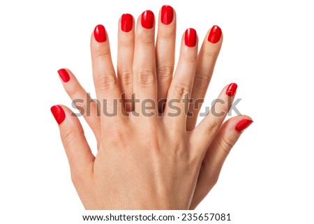 Woman with beautiful manicured red fingernails gracefully crossing her hands to display them to the viewer on a white background in a fashion, glamour and beauty concept
