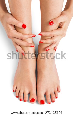 Woman with beautiful neatly manicured red finger and toenails sitting with bare feet clasping her ankles to display her nails, closeup on white in a fashion and beauty concept - stock photo