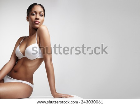 woman with beauty figure sitting on a table - stock photo